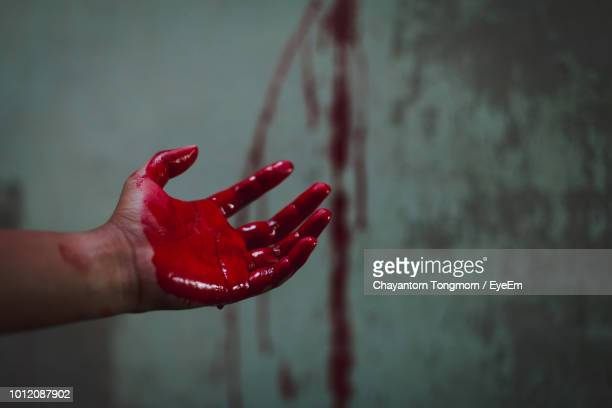 cropped hand of person with blood against wall - human blood stock pictures, royalty-free photos & images