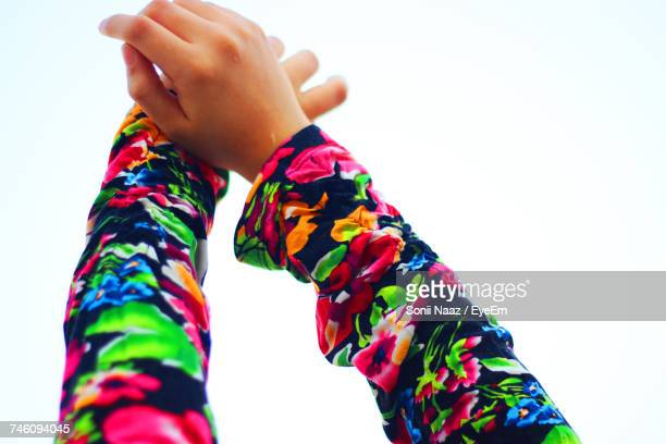 Cropped Hand Of Person With Floral Sleeves Against White Background