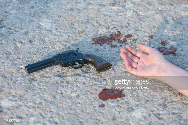 cropped hand of person with gun on land - crime victim stock pictures, royalty-free photos & images