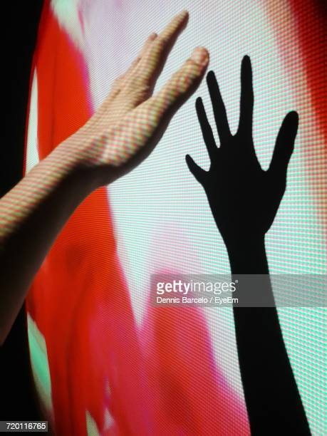 cropped hand of person with shadow on projector - projektion stock-fotos und bilder