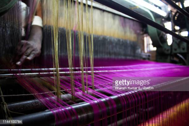 cropped hand of person working on loom in factory - loom stock pictures, royalty-free photos & images