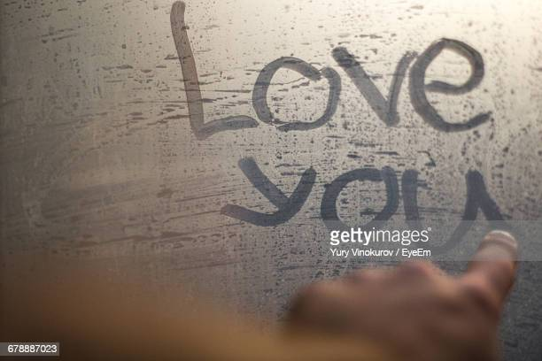 Cropped Hand Of Person Writing Love Message On Frosted Glass