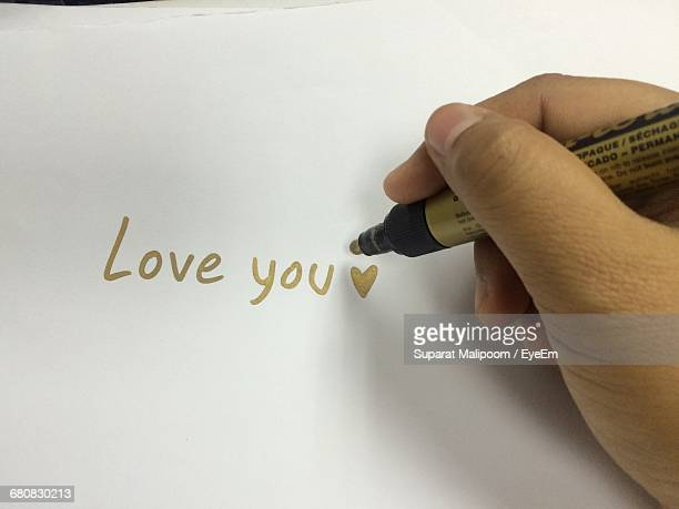 Cropped Hand Of Person Writing Love You On Paper With Gold Colored Felt Tip Pen
