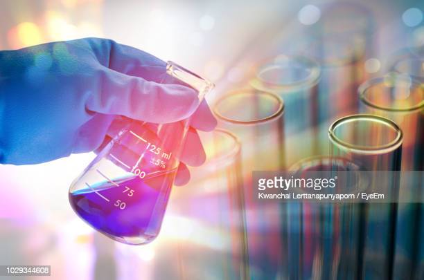 cropped hand of scientist testing chemicals in laboratory - scientificsubjects stock pictures, royalty-free photos & images