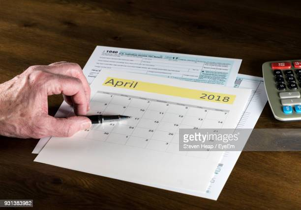 Cropped Hand Of Senior Man With Pen And Calendar On Table