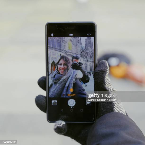 cropped hand of smiling woman taking selfie against man photographing with camera - paire de gants photos et images de collection