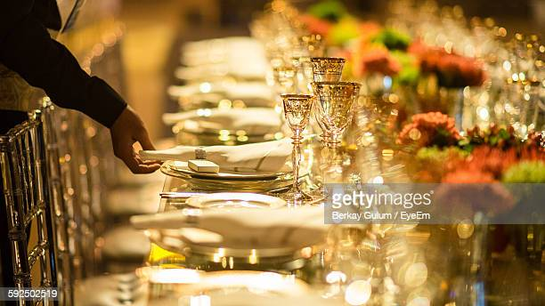 Cropped Hand Of Waiter Arranging Table At Restaurant