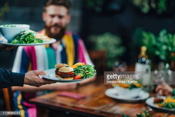 cropped hand of waiter keeping food on table in restaurant - serving size stock photos and pictures