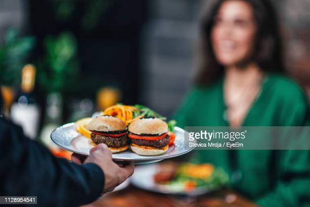 cropped hand of waiter keeping food on table in restaurant - serving size stock pictures, royalty-free photos & images