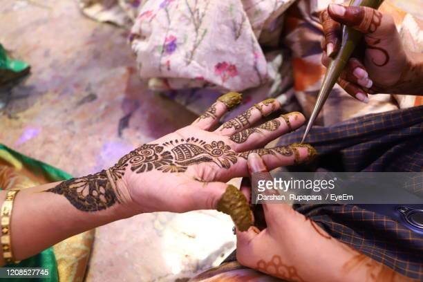 cropped hand of woman applying henna tattoo at home - ceremony stock pictures, royalty-free photos & images
