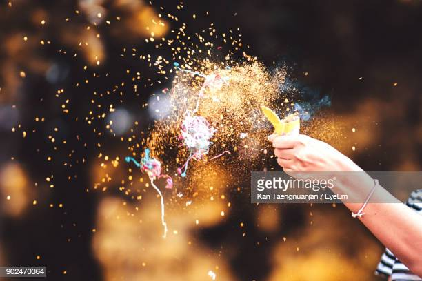 Cropped Hand Of Woman Blowing Confetti