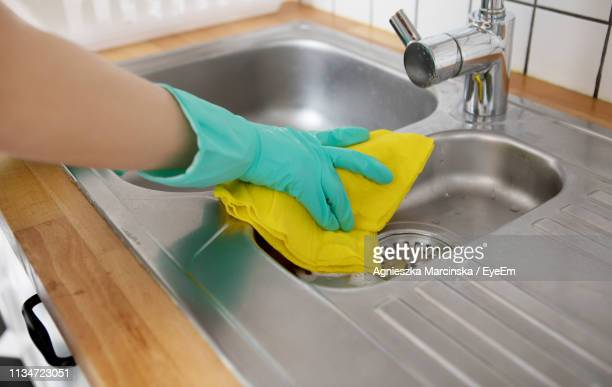 cropped hand of woman cleaning sink in kitchen at home - kitchen sink stock pictures, royalty-free photos & images