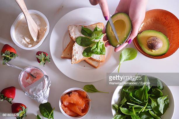 Cropped Hand Of Woman Cutting Avocado With Breakfast Served On Table