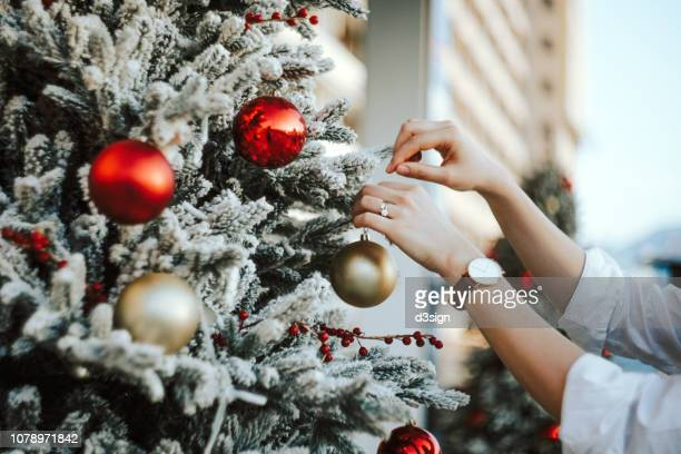 cropped hand of woman decorating and hanging baubles on christmas tree - ornato foto e immagini stock