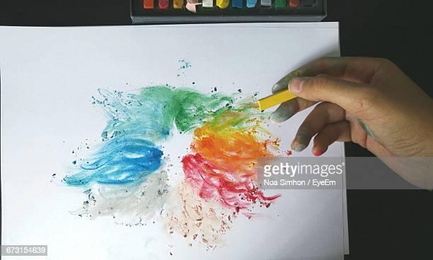 Cropped Hand Of Woman Drawing With Chalk On Paper