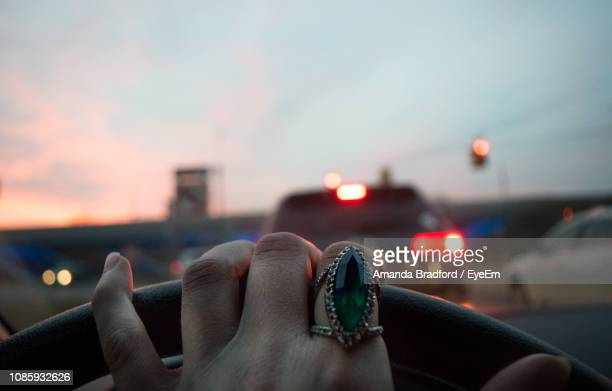 cropped hand of woman driving car during sunset - unusual angle stock pictures, royalty-free photos & images