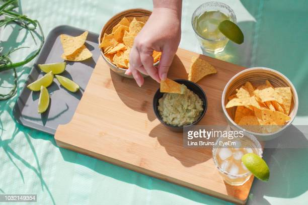 cropped hand of woman eating nacho chips on table - snack stock pictures, royalty-free photos & images
