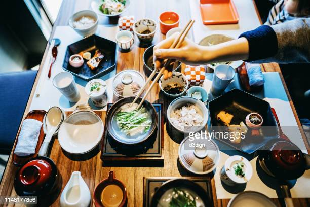 cropped hand of woman enjoying delicate japanese style cuisine with various side dishes, miso soup, seafood and green tea in restaurant - washoku fotografías e imágenes de stock
