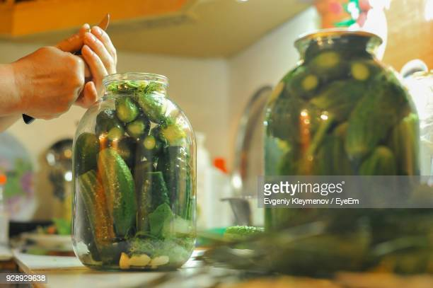 Cropped Hand Of Woman Filling Jar With Vegetables