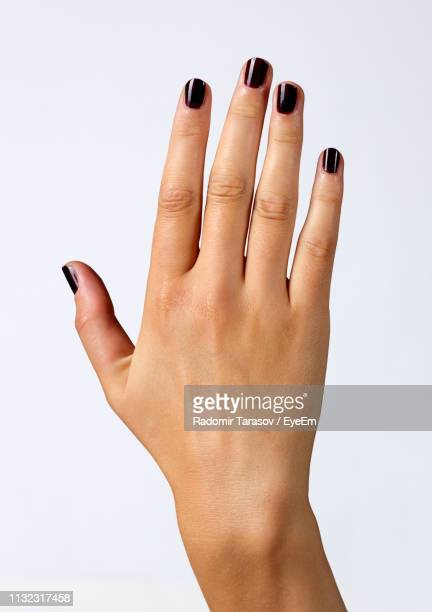 cropped hand of woman gesturing against white background - マニキュア液 ストックフォトと画像