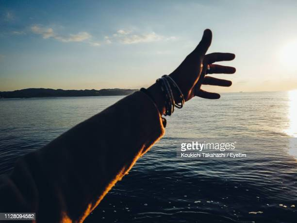 Cropped Hand Of Woman Gesturing At Beach Against Sky During Sunset