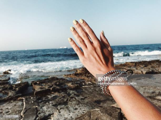cropped hand of woman gesturing at beach against sky - bracelet stock pictures, royalty-free photos & images
