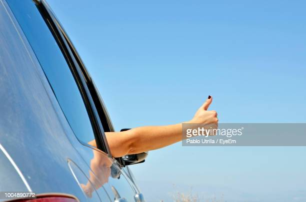 cropped hand of woman gesturing in car window against blue sky - sinal manual - fotografias e filmes do acervo