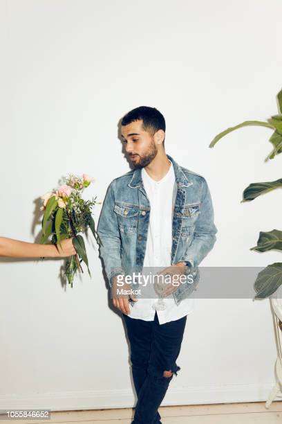 cropped hand of woman giving flowers to young man standing with drink against white wall at home - donner photos et images de collection