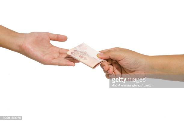 cropped hand of woman giving paper currency to friend against white background - recibir fotografías e imágenes de stock