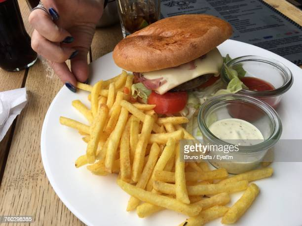 Cropped Hand Of Woman Having Potato Chips And Burger In Plate On Table