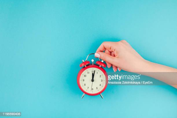 cropped hand of woman holding alarm clock against blue background - time stock pictures, royalty-free photos & images