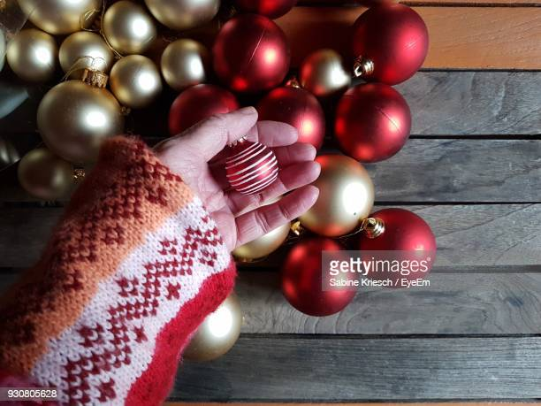 Cropped Hand Of Woman Holding Bauble Over Table