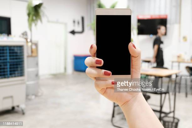 cropped hand of woman holding blank mobile phone in cafe - red nail polish stock pictures, royalty-free photos & images