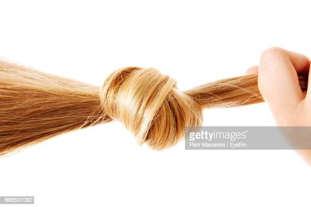 cropped hand of woman holding blond hair against white background - tied knot stock pictures, royalty-free photos & images