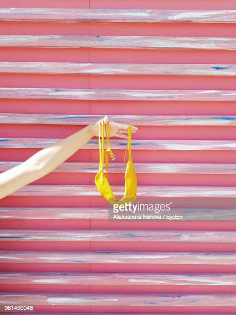 cropped hand of woman holding bra against steps - bra stock pictures, royalty-free photos & images