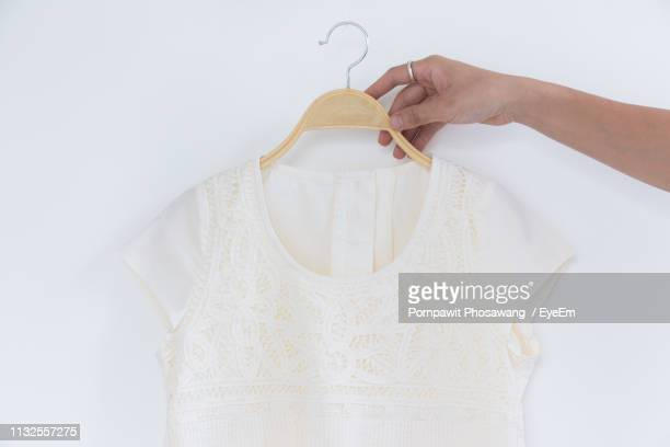 cropped hand of woman holding coathanger with white dress by wall - white dress stock pictures, royalty-free photos & images