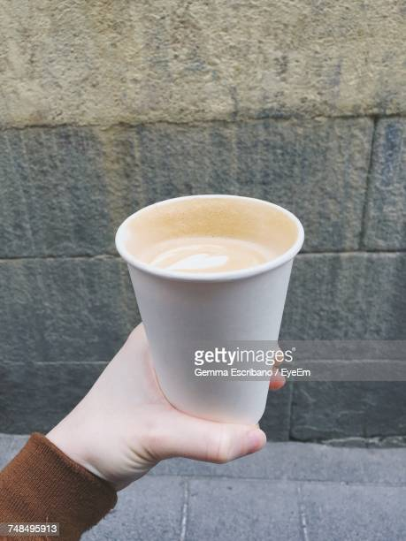 Cropped Hand Of Woman Holding Coffee Cup Against Wall