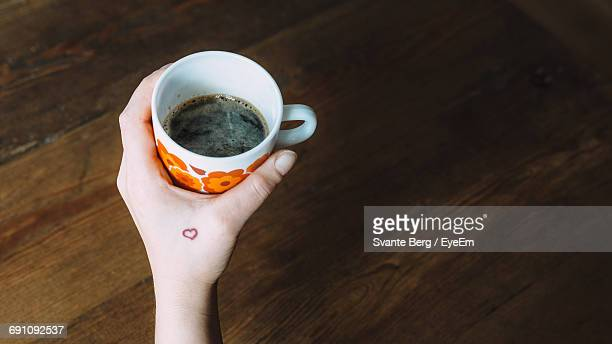 cropped hand of woman holding coffee on wooden table - friedrichshain stock photos and pictures