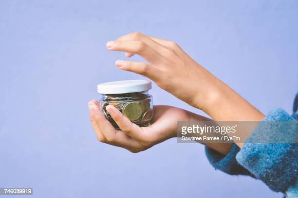 Cropped Hand Of Woman Holding Coins In Glass Container Against Purple Background