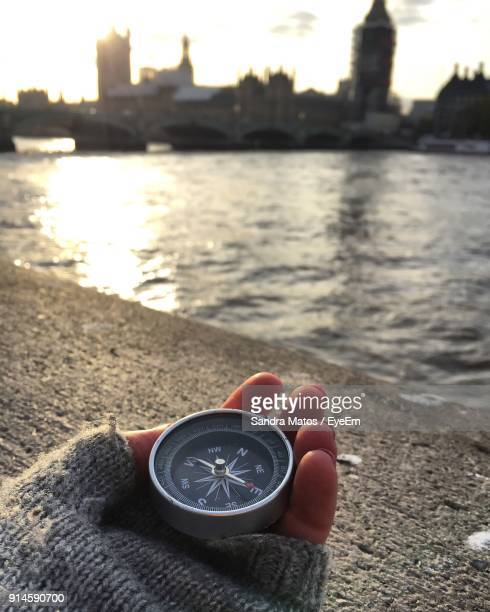 Cropped Hand Of Woman Holding Compass By River In City