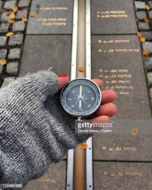 cropped hand of woman holding compass over footpath - greenwich london stock pictures, royalty-free photos & images