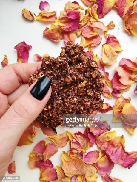 Cropped Hand Of Woman Holding Cookie Over Dried Petals On White Table