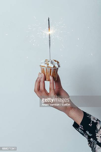 Cropped Hand Of Woman Holding Cupcake With Sparkler Over White Background