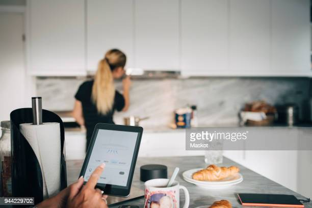 Cropped hand of woman holding digital tablet against teenage girl adjusting home automation in kitchen