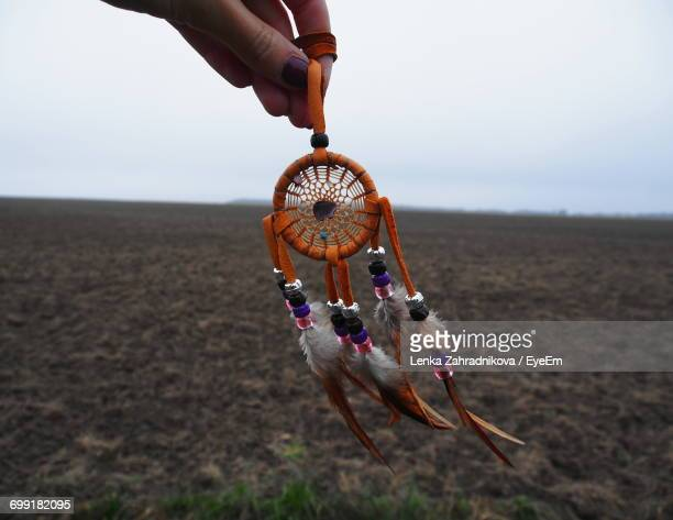 Cropped Hand Of Woman Holding Dreamcatcher Over Field Against Sky
