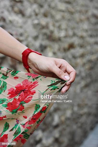 cropped hand of woman holding dress - robe à motif floral photos et images de collection