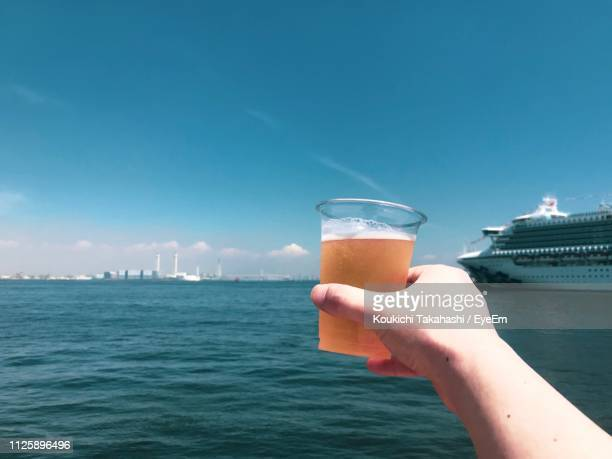 Cropped Hand Of Woman Holding Drink Over Sea Against Sky