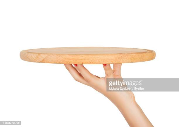 cropped hand of woman holding empty cutting board against white background - chopping board stock pictures, royalty-free photos & images