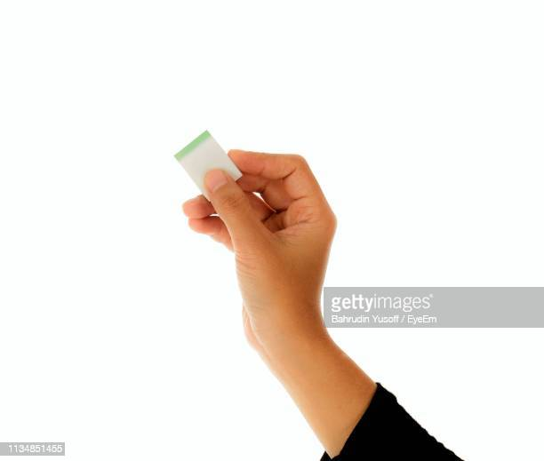 cropped hand of woman holding eraser against white background - eraser stock pictures, royalty-free photos & images