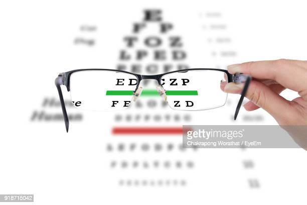 cropped hand of woman holding eyeglasses over chart - eye chart stock pictures, royalty-free photos & images